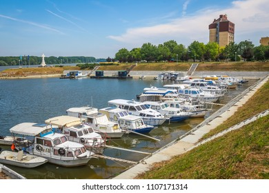 VUKOVAR, CROATIA - MAY 14, 2018 : A view of boats moored on the coast of the river Dunav with the Hotel Dunav and the cross in memory of croatian war defenders in the background in Vukovar, Croatia.