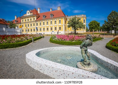 VUKOVAR, CROATIA - MAY 14, 2018 : View of a water fountain with statue and flowers in a park with the City museum located in the Eltz castle in the background  in Vukovar, Croatia.