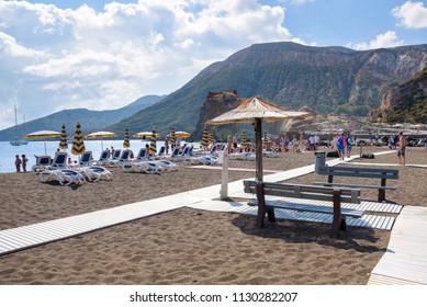 Vulcano Island, Italy - September 9, 2016: People sunbathe on the beach on Vulcano Island, one of the volcaninc islands of Aeolian archipelago