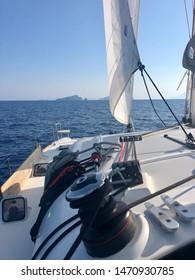 Vulcano, Italy - Circa July 2019: A catamaran sails towards the Aeolian island of Vulcano, off the north coats of Sicily. The Aeolian islands are a popular itinerary for yachting and flotilla vacation
