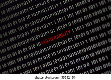 'Vulnerability' word in the middle of the computer screen surrounded by numbers zero and one. Image is taken in a small angle.