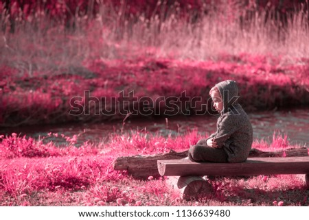 Vulnerable boy sitting at the river side