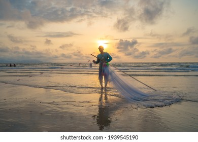 Vung Tau, VIETNAM - 20 MAR 2021: Fisherman casting his net at the sunrise or sunset. Traditional fishermen prepare the fishing net