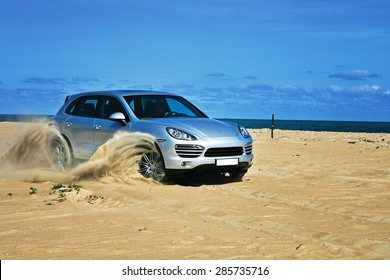 Vung Tau, Vietnam - April 20, 2012: A luxury sport car running on sand terrain of the beach side under the sunlight in a off-road test drive.