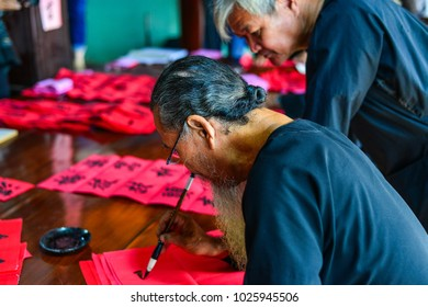 Vung Tau, Vietnam - Feb 6, 2018. Old men writing Chinese calligraphy on red paper at local village in Vung Tau, Vietnam.