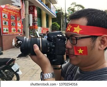 VUNG TAU, VIETNAM - JANUARY 27, 2018: A Vietnamese fan photographs other fans watching the final of the 2018 AFC U 23 Championship. Uzbekistan defeated Vietnam in the final to win their first title