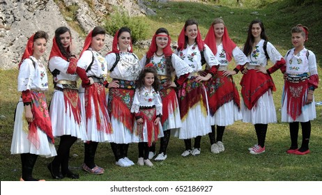 VUSANJE, MONTENEGRO - JULY 21, 2015: female components of albanian folk group dressed with colorful traditional costumes is posing in Montenegro near the border with North Albania