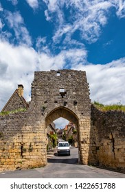VW van in Domme, France - May 3, 2019: small campervan driving through ancient city gates.