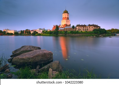 Vyborg Castle. The Tower of St. Olav. Reflection of the castle in the water. Stones in the foreground. Travel destinations in Russia.