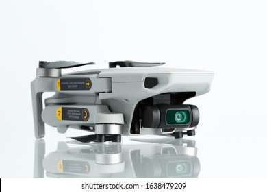 Vyborg / Russia - February 03, 2020: Dji mavic mini stands on a white mirror table white background. Side view.