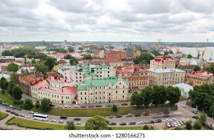 Vyborg, Russia - July 17, 2016: Panorama of the city with beautiful houses with multi-colored roofs from the tower of Olaf of Vyborg Castle. View of the road with cars and tourist buses.