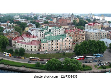 Vyborg, Russia - July 7, 2012: Panorama of the city with beautiful houses with multi-colored roofs from the tower of Olaf of Vyborg Castle. View of the road with cars and tourist buses. Aerial view