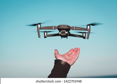 Vyborg, Russia - June 10, 2019 : Dji Mavic 2 pro flies in the air. Object in focus. In the frame of the hand of a man to catch the drone
