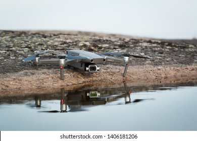 Vyborg, Russia - May 19, 2019 : Dji Mavic 2 pro on a stone near the water. Reflection of a drone in the water. The object is in focus. Background blurred
