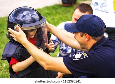 Vynnytsa. Ukraine. 07.07.2018. The child in a police helmet.good attitude of police officers to children. The concept Police loves children. The cop has helped the child to try on the police officer's