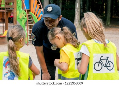 Vynnytsa. Ukraine. 09.15.2018 The police officer explains traffic regulations to girls. The cop talks and helps citizens. The concept Police loves children.