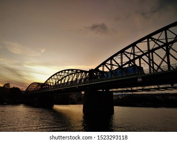 Vysehrad Railway Bridge with train passing by during sunset. The bridge connects Prague neighborhoods of Vyton and Smichov. Popular architectural landmark of Prague, Czech Republic.