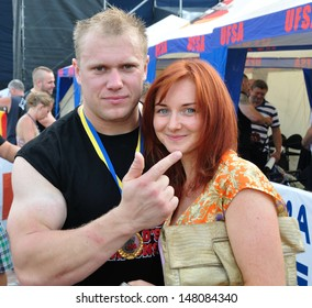 VYSHGOROD, UKRAINE - 28 JULY 2013: The champion Ben Kelsey makes photos with unknown woman on Strongmen Worlds Championship on 28 July 2013 in Vyshgorod, Ukraine.
