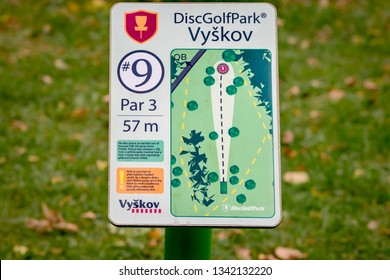 VYSKOV, CZECHIA – SEPTEMBER 9, 2018: A disc golf target with basket, chains and yellow top in a park, for public sport and games