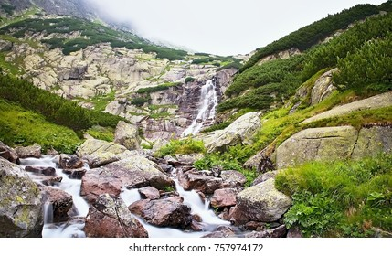 Vysoke Tatry, Slovakia - view of the waterfall Skok. Sky, fog, mountain river and knee timber at the waterfall Skok in Vysoke Tatry, Slovakia.