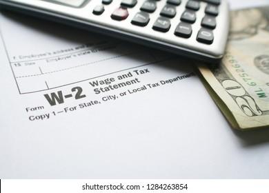 W-2 Tax Form With Calculator & Twenty Dollar Bill