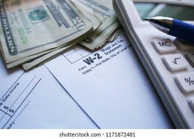 W-2 Tax Form With Twenties, Calculator & Pen