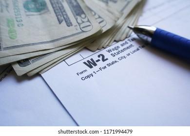 W-2 Tax Form With Twenties & Pen