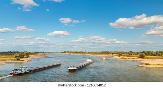 The Waal river near Nijmegen with cargo ships passing by in The Netherlands