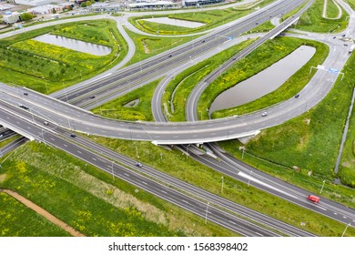 Waalwijk, Netherlands - may 5 2019: A cloverleaf highway with traffic in the middle of green fields.