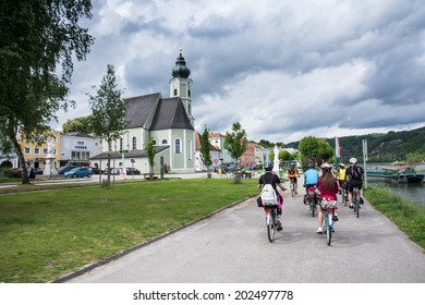 wachau Valley,Austria-May 9,2014:a group of cyclists through a village on the banks of the Danube on the famous Austrian bike path during a cloudy day