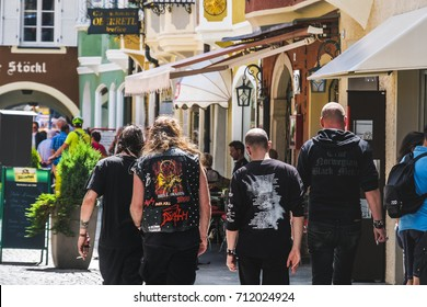 Wacken, Germany, Aug 13 2017: Heavy Metal guys fans, metalheads walk in the street seen from behind. Alternative music lifestyle
