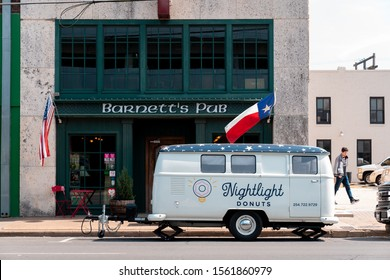 WACO, TEXAS - MARCH 22 2019: Central city Waco showing wear and age. Barnett's Pub and Nightlight Donuts two staples are shown with American and texan flags hanging. The food truck covers the facade.