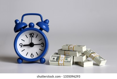 The wad of $100 bills in front of a blue alarm clock.