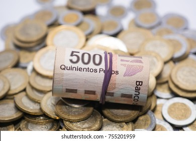wad of 500 mexican pesos bills on some coins