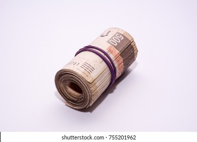 wad of mexican peso bills on white background