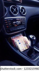 Wad of money in a luxurious car. Succeed. Many euros on the dashboard