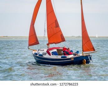 WADDENSEA, NETHERLANDS - AUG 23, 2017: People sailing on sailboat on Wadden Sea near coast of West Frisian island Ameland, Friesland