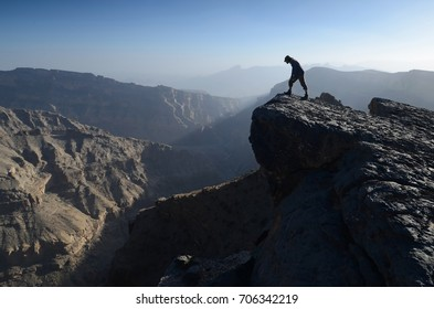 Wadi Ghul, Grand Canyon of Arabia with standing silhouette of tourist, Oman