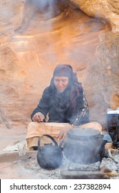 WADI MUSA, JORDAN - NOVEMBER 18, 2012: Old woman cooking tea for tourist on desert sands of ancient Petra city. Petra is historical and archaeological city and famous for its rock-cut.