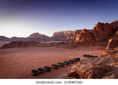 Wadi Rum desert, Jordan. Beautiful aerial view of bedouin camp at sunset from above with tents lined up and red rock formations landscape.