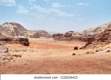 Wadi Rum desert, Jordan,  The Valley of the Moon. Orange sand, haze, clouds. Designation as a UNESCO World Heritage Site. National park outdoors landscape. Offroad adventures travel background.