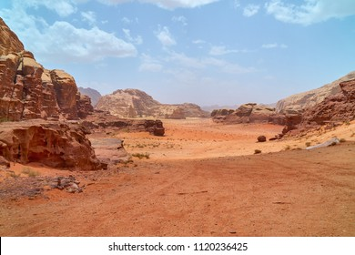 Wadi Rum desert, Jordan, The Valley of the Moon. Orange sand, haze, clouds. Designation as a UNESCO World Heritage Site. Red planet Mars  landscape. Offroad adventures travel background.