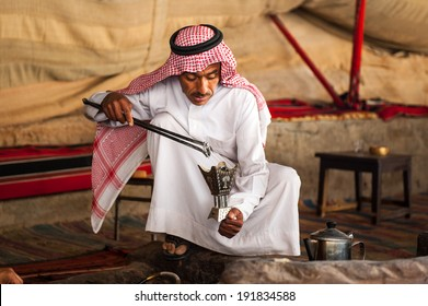 WADI RUM, JORDAN - APR 30, 2014: Unidentified bedouin shows the process of making tea the traditional way. Bedouins are a part of a desert-dwelling Arabian ethnic group