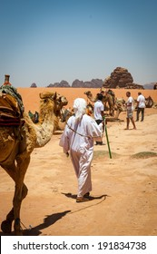 WADI RUM, JORDAN - APR 30, 2014: Unidentified bedouin walks with a camel in the desert of Wadi Rum. Bedouins are a part of a desert-dwelling Arabian ethnic group