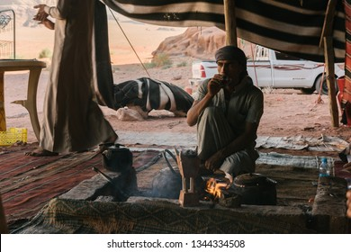 WADI RUM, JORDAN - AUGUST 17, 2016: unidentified young man take a tea near a fireplace under a beduin tent