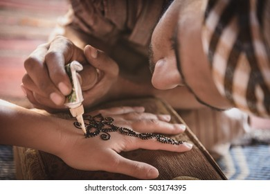 WADI RUM, JORDAN - AUGUST 17, 2016: unidentified bedouin making henna on a woman's hand. Hand decorations are usually done by a relative of the bride in her home