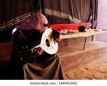 Wadi Rum, Jordan - circa April 2015: Bedouin man playing the guitar in a campsite in Wadi Rum desert, Jordan