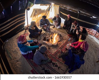 Wadi Rum, Jordan – January 25th 2020: Wadi Rum bedouis and tourists in traditional bedouin tent around fire