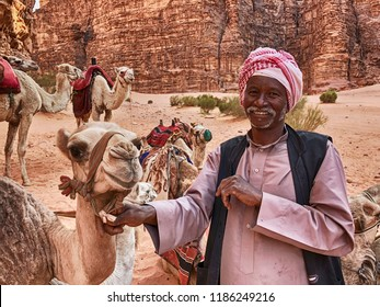 WADI RUM, JORDAN - JUNE 14, 2016: A smiling Bedouin camel herder holds one of his camels in the canyons of the Wadi Rum desert in Jordan.