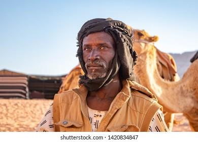 Wadi Rum, Jordan - May 15, 2019: Bedouins tending to camels in the Wadi Rum desert of Jordan during Ramadan.